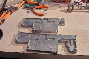 The                 cast aluminum shield covers. The lower cover is                 unmodified, but the upper casting has the portion that                 covers the amplifier section removed.
