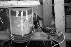 View of the CT transmitter and its loading coil, atop its protective garbage can located at the base of the antenna mast